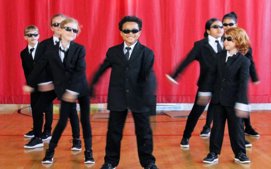 Group of young children wear suits while flossing
