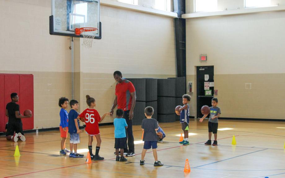 Man coaches young children in basketball