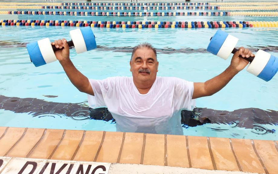 Man lifts water weights while in pool