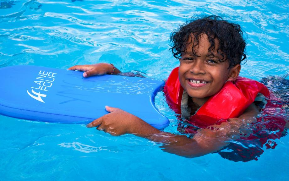 Young boy holds kickboard in pool