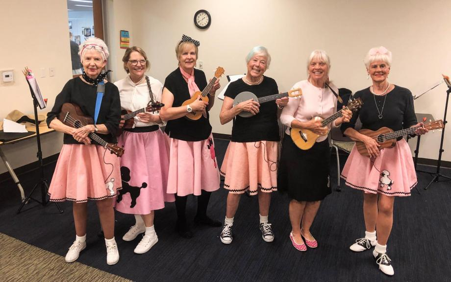 Group of older women wear poodle skirts and hold ukeleles