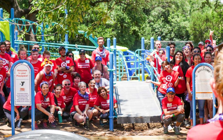 Group of volunteers in red shirts pose near playground