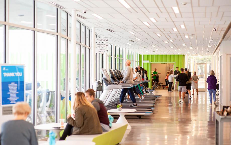 YMCA members use treadmills in windowed hallway