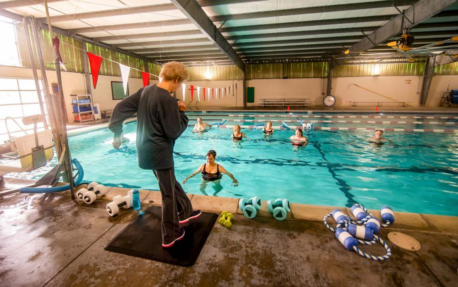 Woman stands on edge of pool to lead water aerobics class