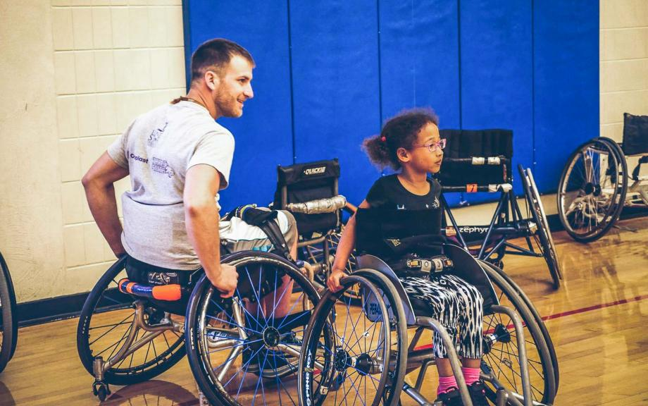 Man and young girl in wheelchairs in gymnasium