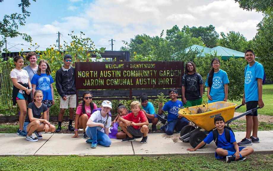 A group of teens stand outside the community garden at the North Austin YMCA