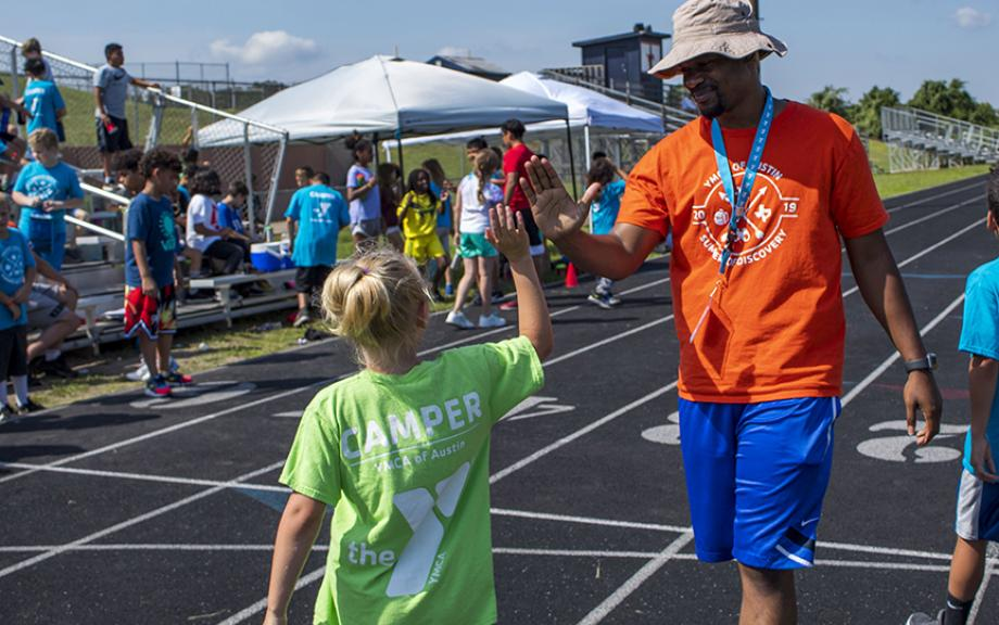 A camp counselor and a camper high 5 after a track and field event