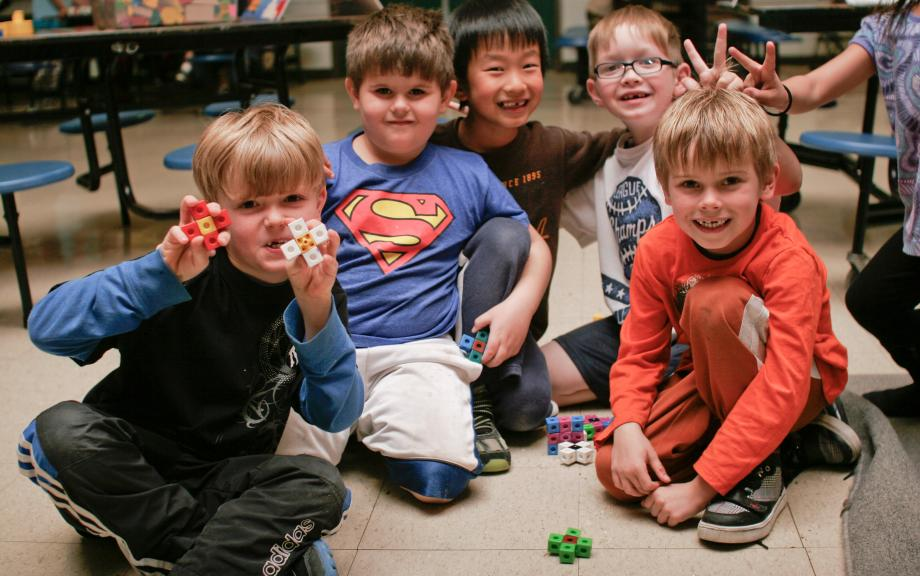 A group of 5 boys show off their block creations and smile for the camera
